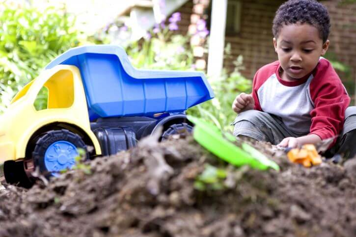 child playing with gardening toys outside