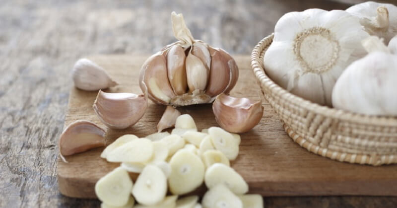 multiple garlic cloves and heads on a table
