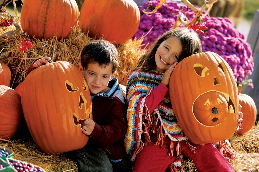 two children happily holding two huge jack-o-lanterns made of pumpkins