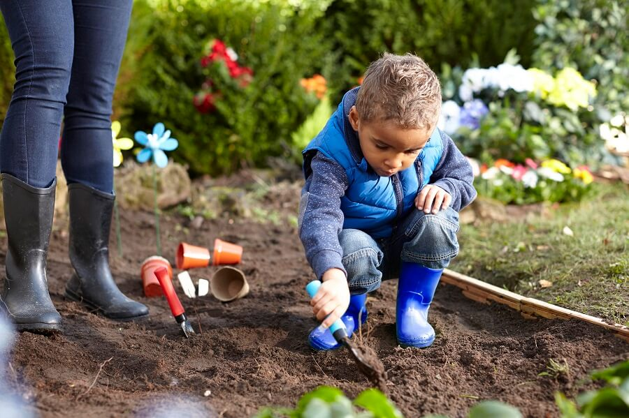 small child playing in the dirt with a shovel