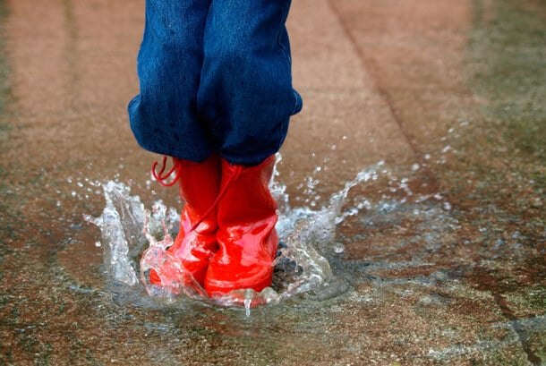 child wearing red rain boots jumping in a puddle