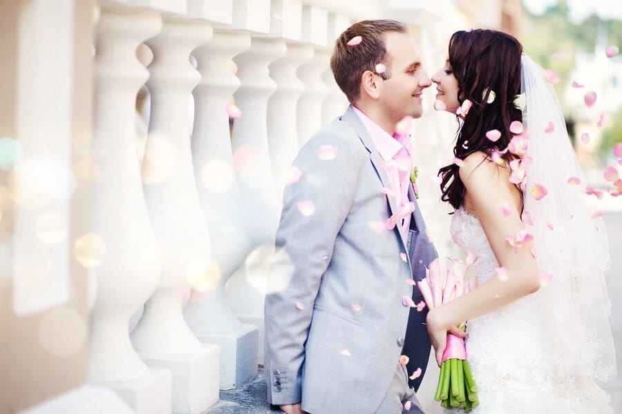 newlyweds smiling happily while surrounded by rose petals