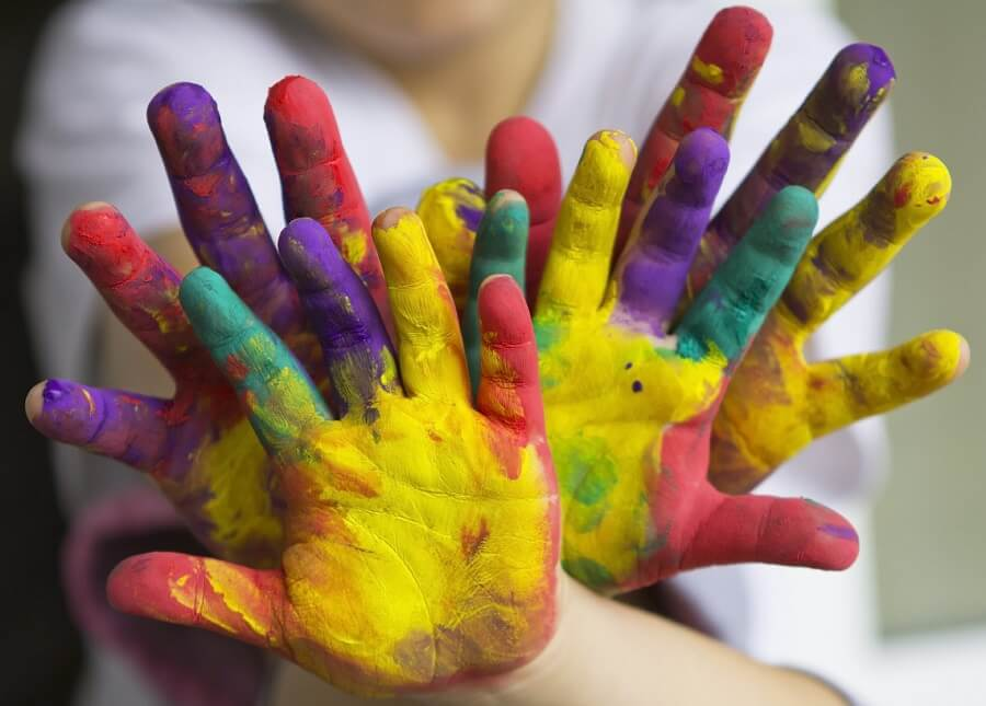 parent and child hands covered in paint