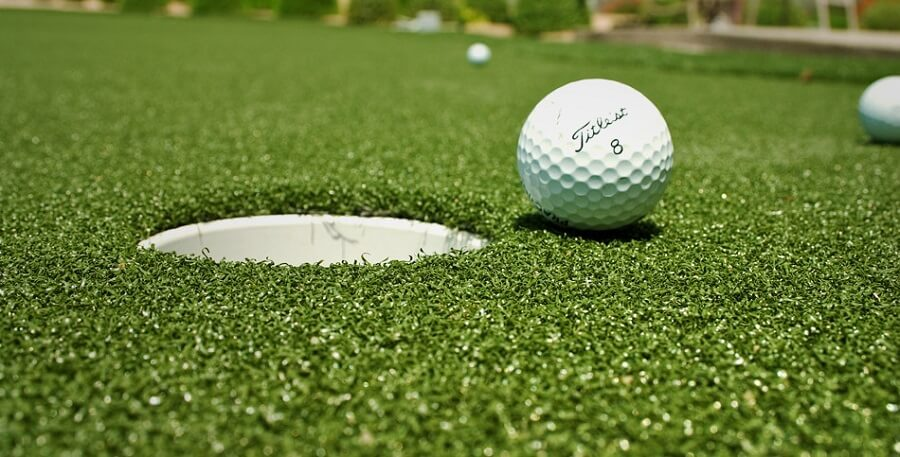 close up image of a ball about to enter a hole on a gold course