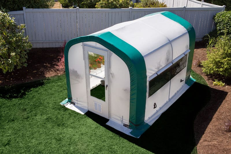 small portable greenhouse in a backyard