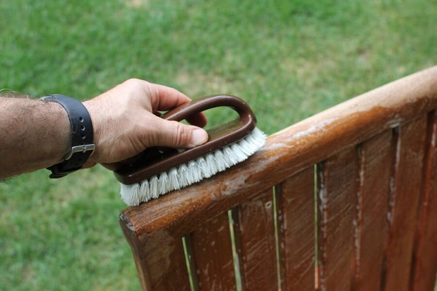 man using a brush to scrub outdoor furniture