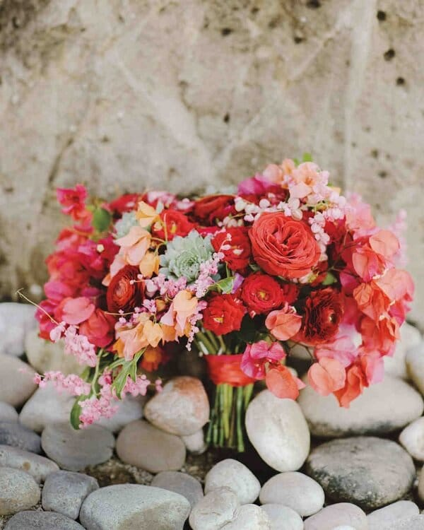 red wedding bouquet sitting on some rocks