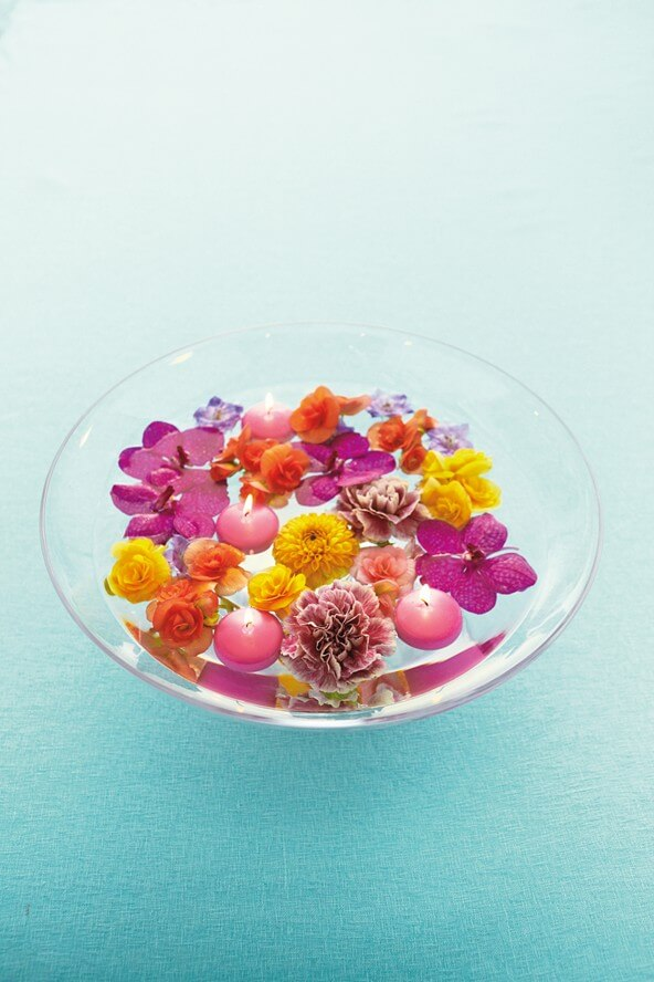 water bowl filled with flower petals and candles