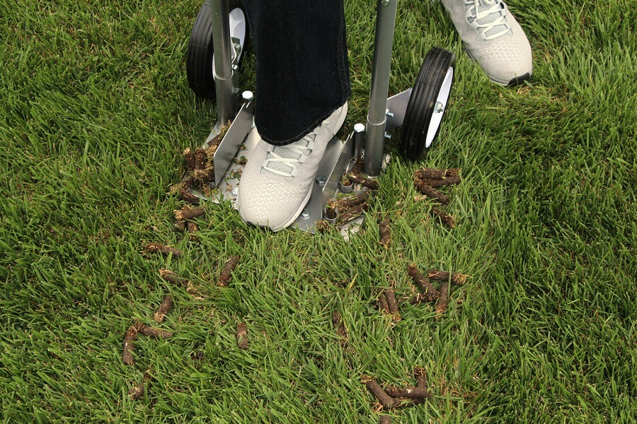 person using a machine to aerate the lawn