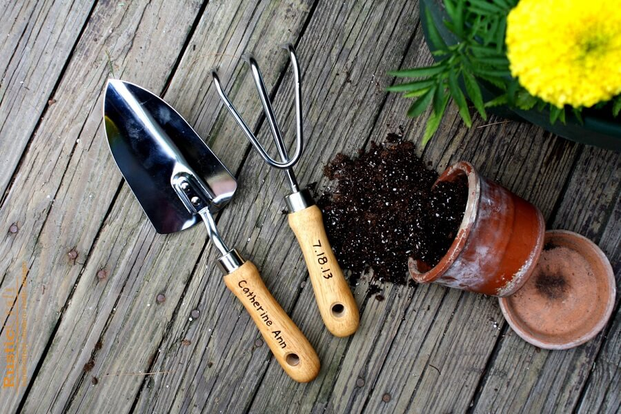 two gardening tools next to a knocked over flower pot