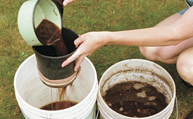 someone using a strainer to get compost tea