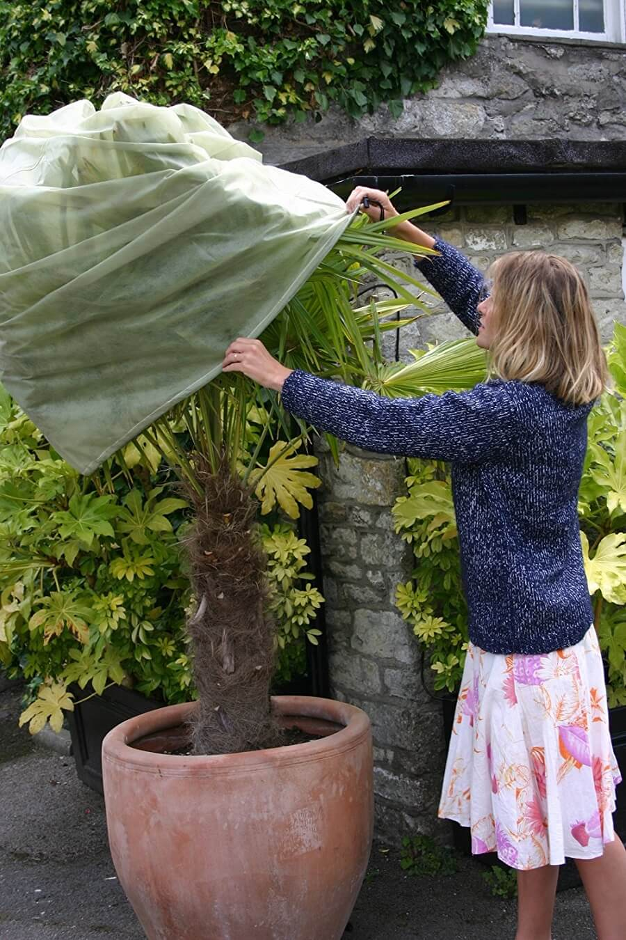 woman using a plant jacket to cover a tree
