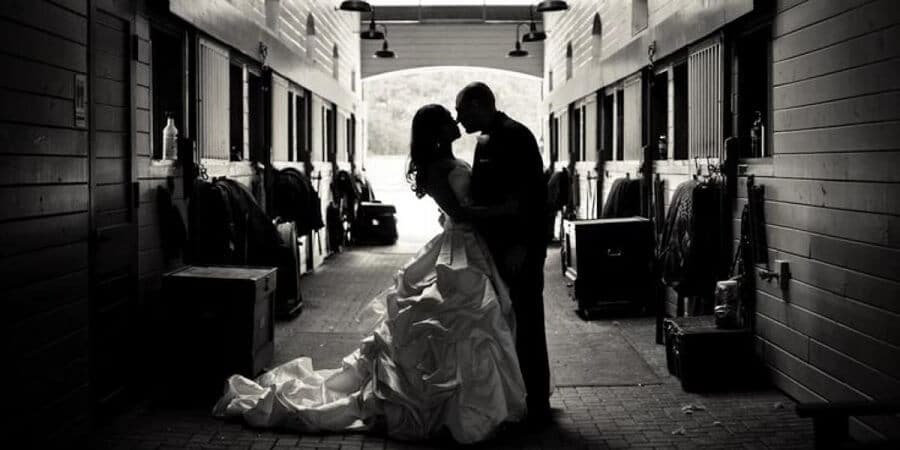 bride and groom posing at the stables