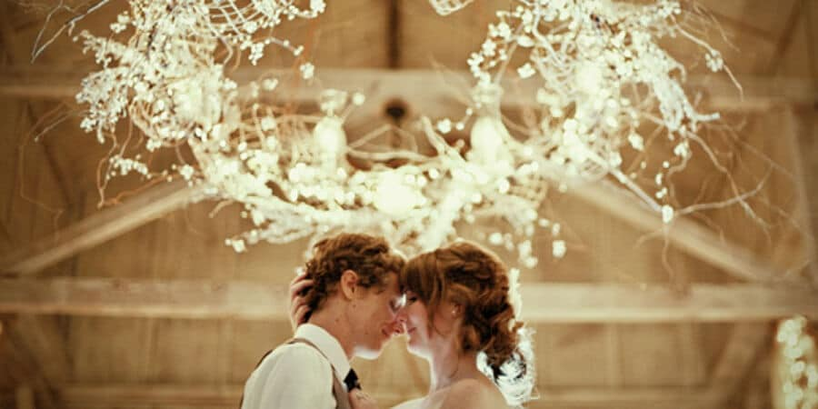 bride and groom hugging and smiling under fairy lights