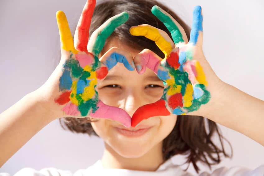 child making a heart with her paint covered hands