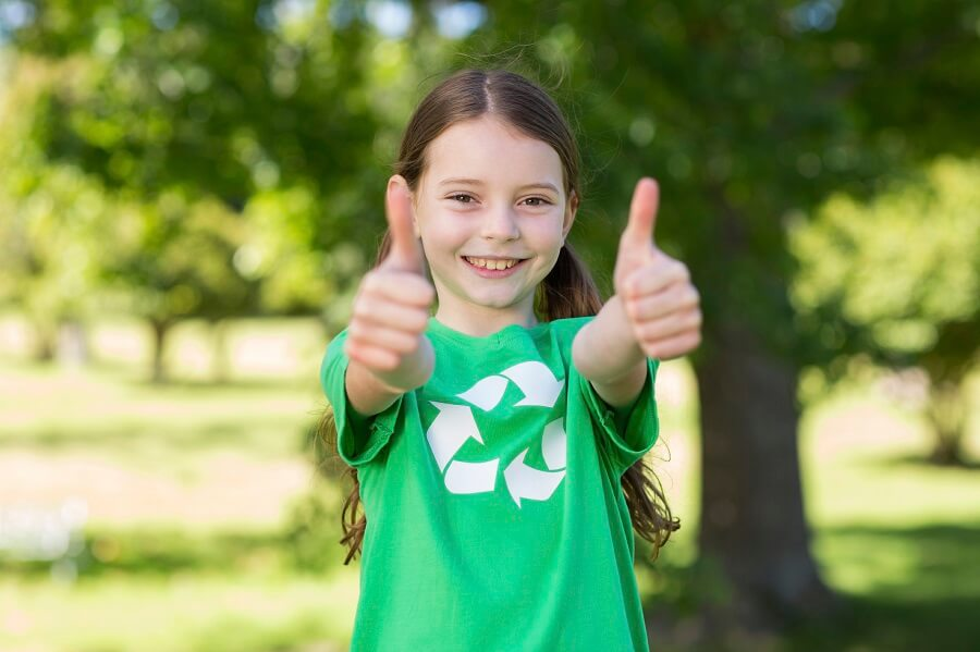 little girl with green shirt showing two thumbs up