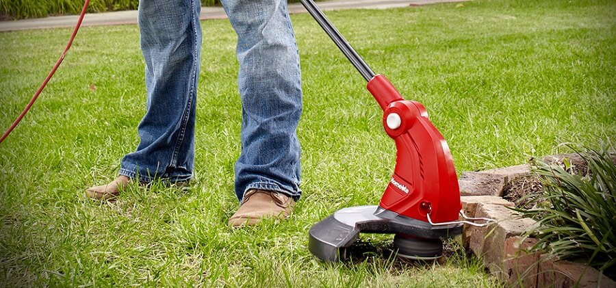 using string trimmer to cut the grass