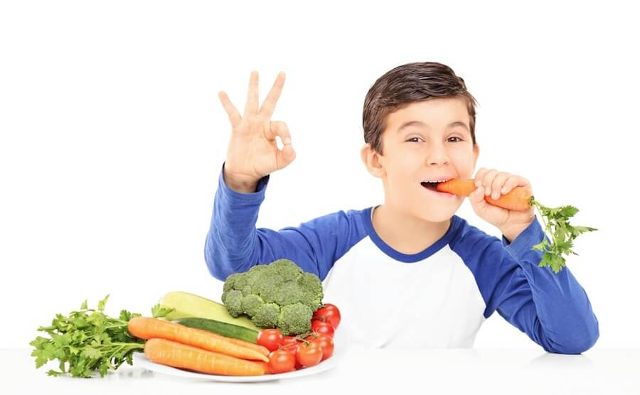 child showing the OK sign while eating a carrot, gardening lesson plans