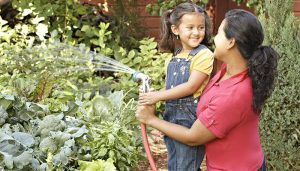 gardening with children, gardening resources, gardening, girl watering plants with her mom