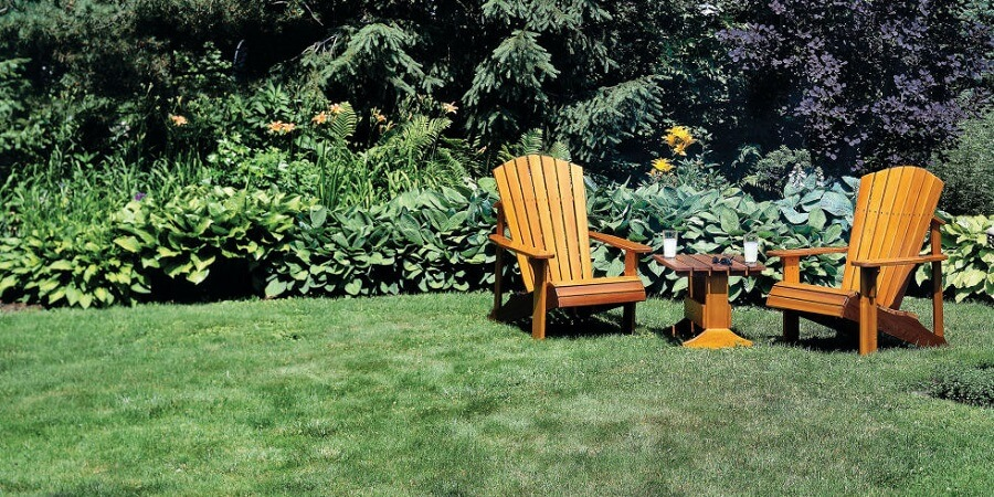 adirondack chairs and a table on a lawn