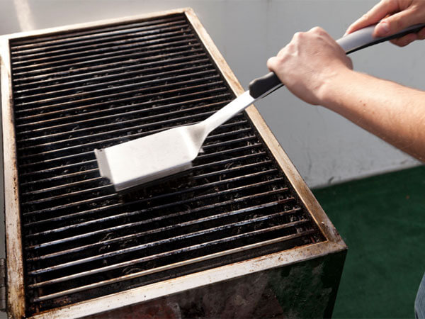 someone cleaning a grill, spring cleanup