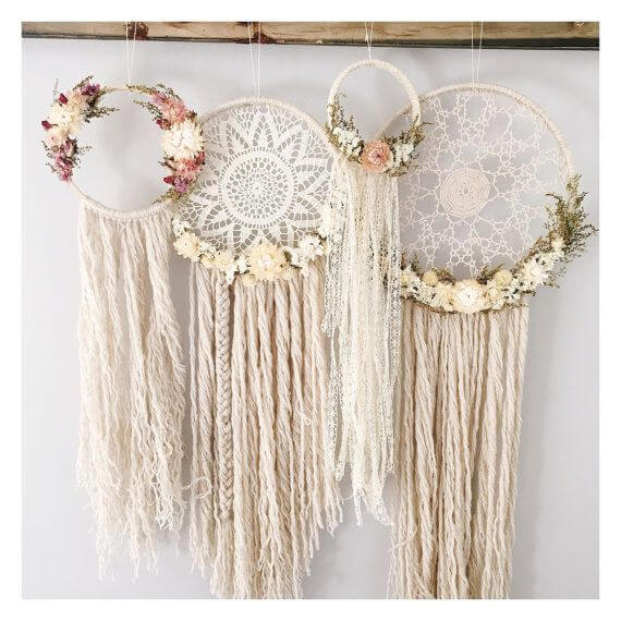three dreamcatchers with dried flowers in them