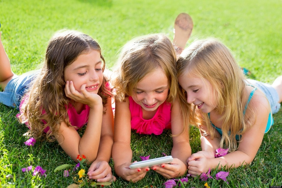 three girls looking at a smartphone