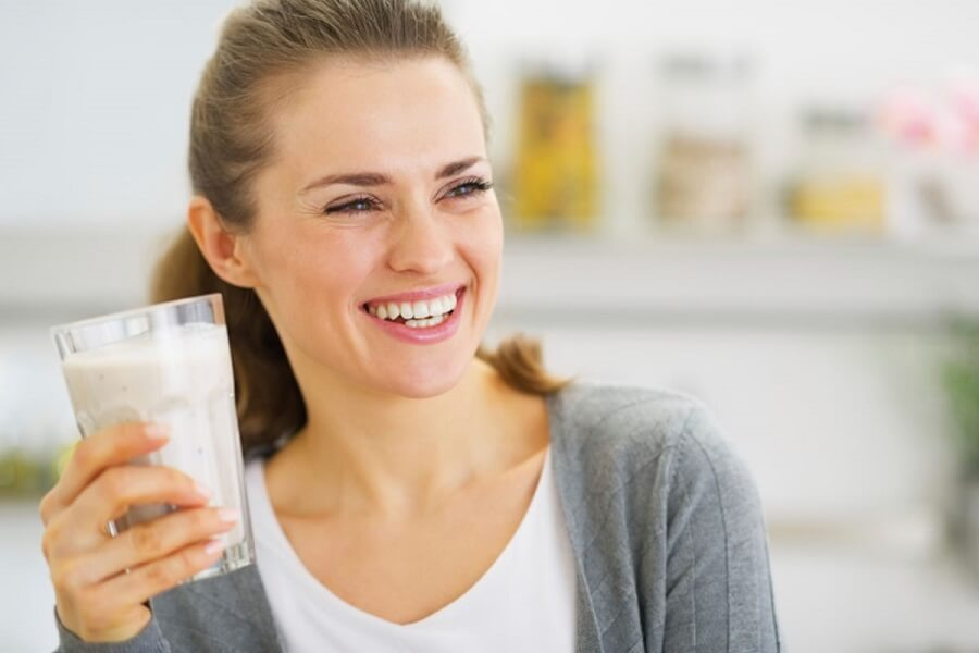 woman laughing while holding a glass