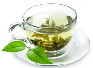 cup of tea with green leaves in it