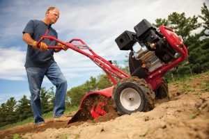 man using a garden tiller on land