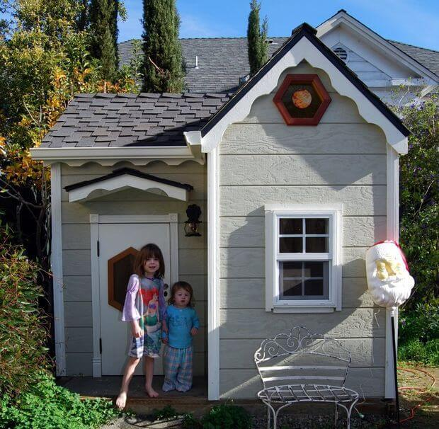 two children standing in front of a playhouse