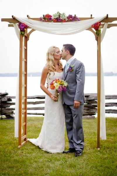 newlyweds kissing in front of a trellis
