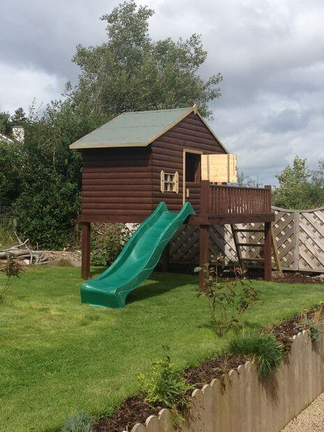 outdoor playhouse that includes a slide