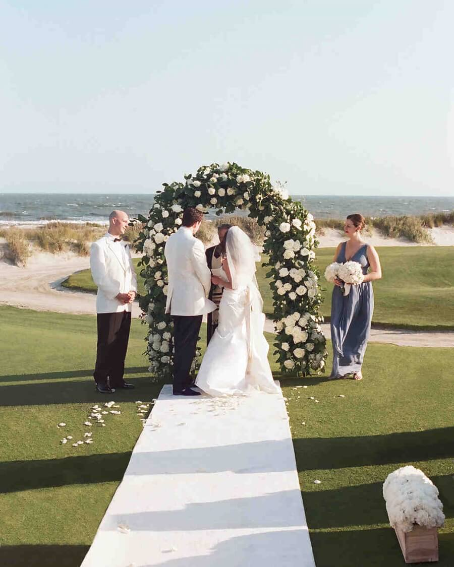 wedding being performed in front of a trellis