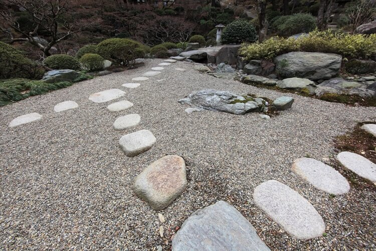Gravel lawn with stepping stones and greenery on the edges