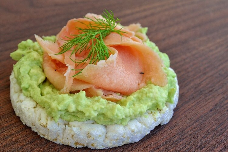 Avocado guacamole on a rice cake with smoked salmon on tip and a bit of dill