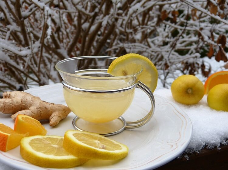 A cup of ginger tea with ginger and lemon next to it