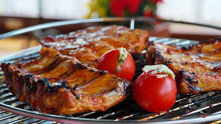 Meat and tomatoes placed on a barbecue grill