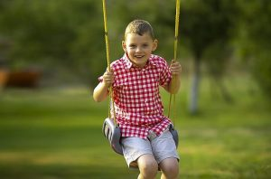 Toddler swinging outdoors