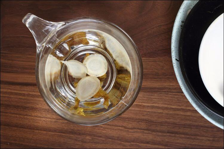 Ginseng root sliced for cooking, placed a transparent plastic cup next to another pot