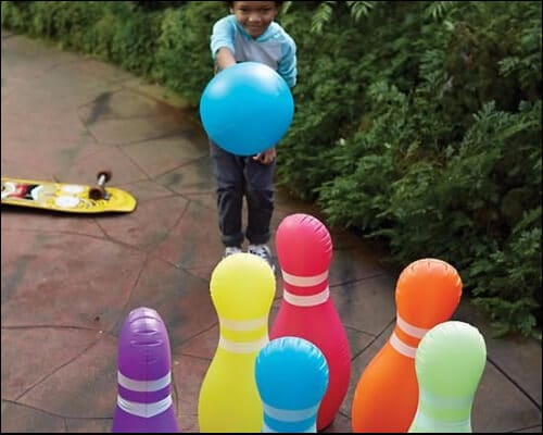 Child throwing a blue inflatable bowling ball towards colorful bowling pins