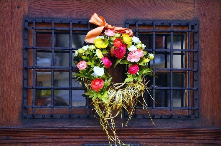 Wreath full of flowers, greenery and a ribbon at the top