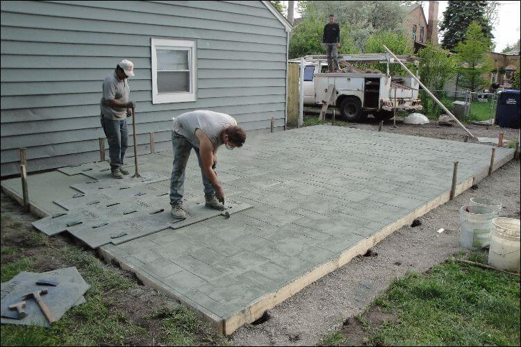 Two men stamping concrete in a backyard
