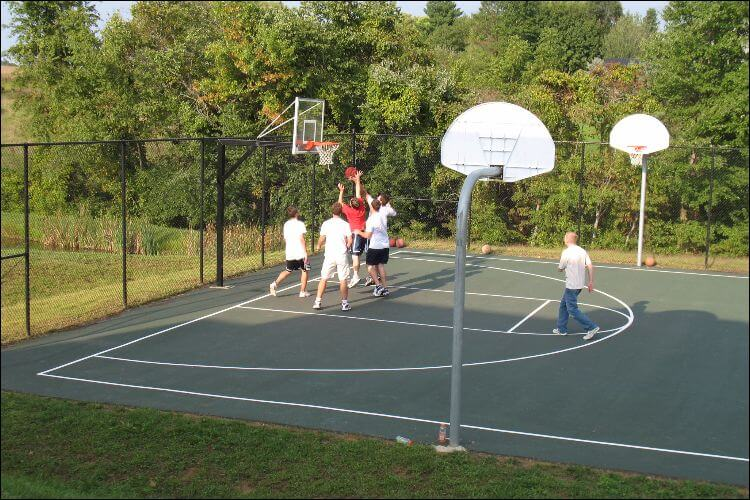 Side shot of a basketball court where several adults are playing