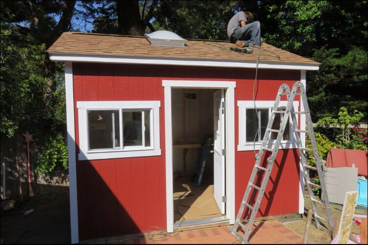 Finishing up the roof of a red shed with white door and windows