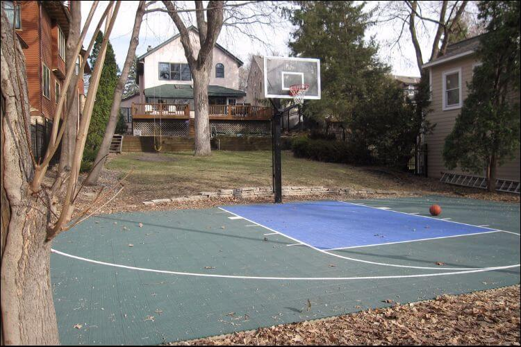 Backyard basketball court with a hoop and surfacing, as well as trees and a house in the background