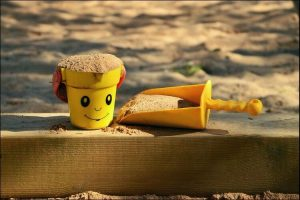 Close up of a yellow toy bucket and shovel filled with sand next to a sandbox