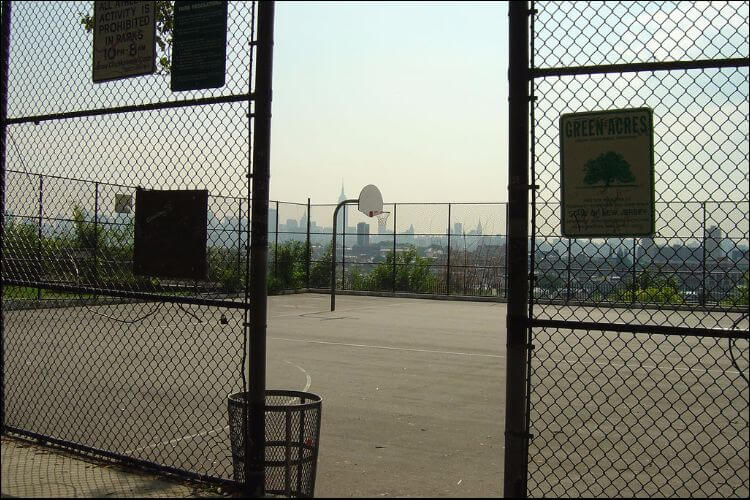 Image of a basketball court with a concrete base, surrounded by tall fences