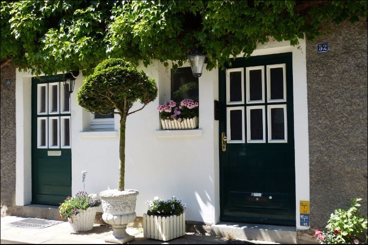 Beautiful shed with white walls and two pretty doors, surrounded by greenery and flowers