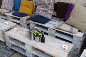 Outdoor set of pallets couch and table in a white color, with colorful back pillows on the couch and ashtrays and a flower pot on the table